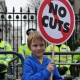 Facebook image of young boy outside Downing Street with a placard saying 'no cuts'.