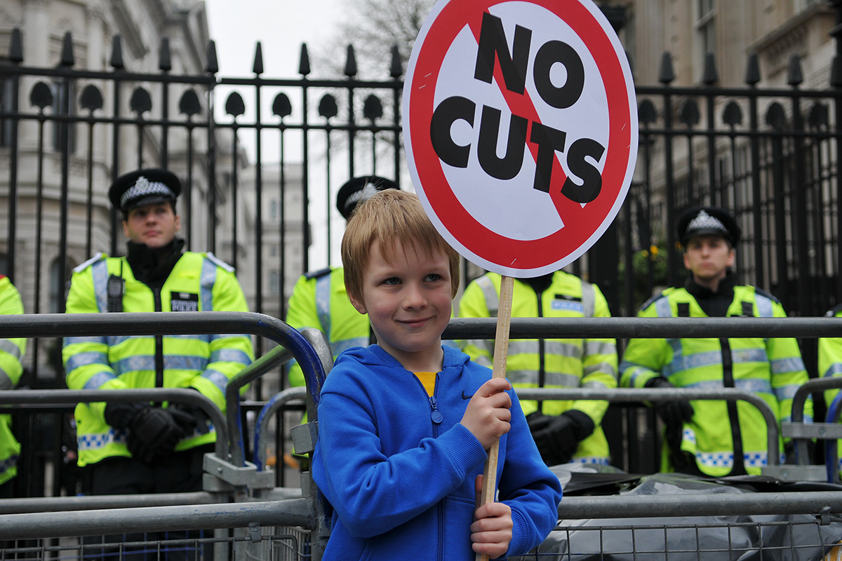Boy holding placard outside 10 Downing Street saying 'no cuts'.