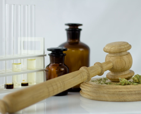 Cannabis oil with apothecary jar and wooden judge hammer.