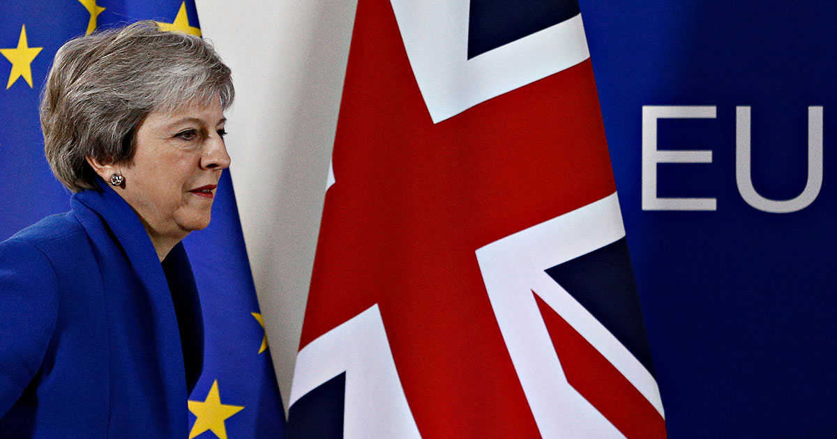 Theresa May, making a hash of Brexit with EU and Union Jack flags.