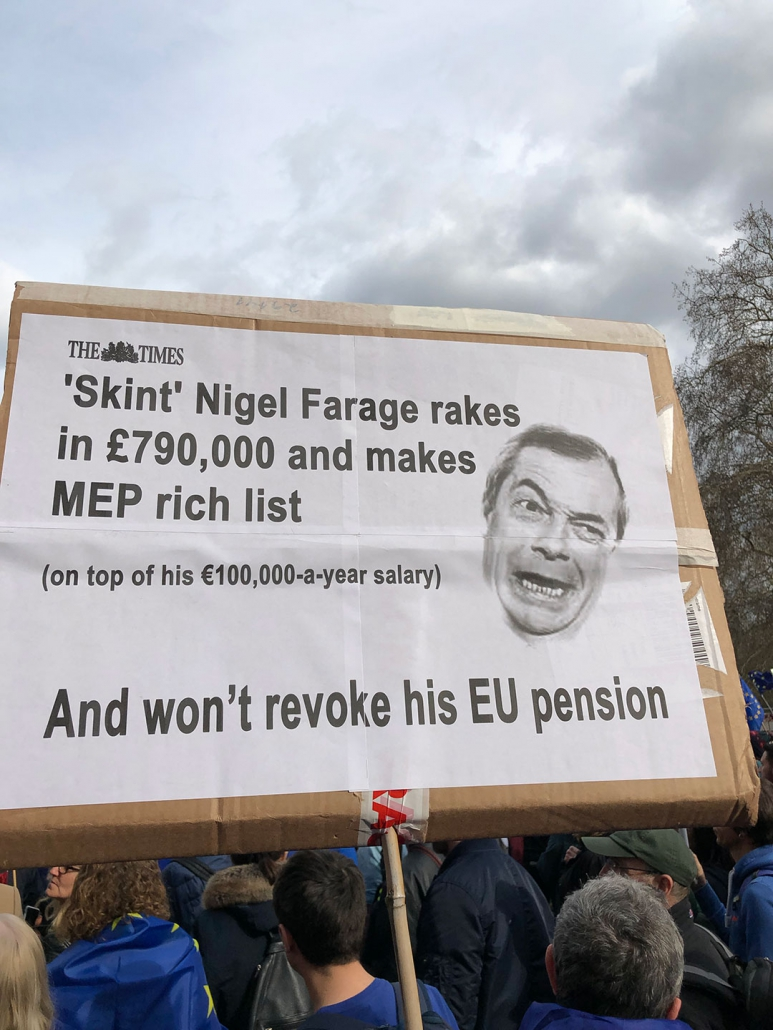 "Placard from London 2019 anti Brexit march saying: ""Skint Nigel Farage rakes in £790,000 and makes the MEP rich list on top of his €100,000-a-year salary and won't revoke his EU pension."