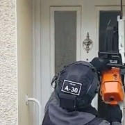 A policeman cuts down a door using a chainsaw.